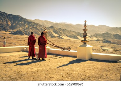 Thiksey, Ladakh - circa November 2011: Photo of two monks blowing horns at rooftop as morning ceremony at Thiksey monastery, Ladakh. In background with beautiful scenery. Documentary editorial.