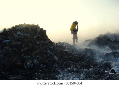 THILAFUSHI, MALDIVES - 11/01/2012: Expatriate worker running with scrap metal over burning trash