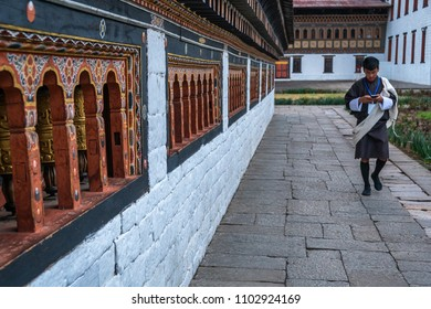 Thimphu, Bhutan - March 30, 2018 : Clerk in traditional dress walking in the inner court of the Tashichho Dzong in Thimphu