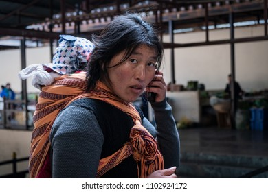 Thimphu, Bhutan - March 30, 2018 : A mother with her baby doing her shopping inside the traditional market of Thimphu