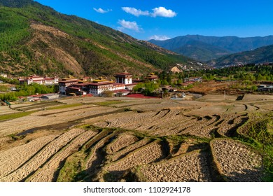 Thimphu, Bhutan - March 30, 2018 : The Tashichho Dzong in Thimphu seen from the road above, with dry rice terraces in the foreground