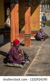 Thimphu, Bhutan - March 31, 2018 : Old people asking for money at the big prayer wheels of the Memorial Chorten in Thimphu
