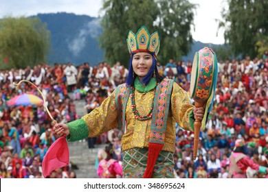 THIMPHU, BHUTAN - SEPTEMBER 25, 2015: Smiling traditional Bhutanese woman dancer with drum and Dakini's hat during Thimphu Tshechu.