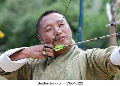 THIMPHU,BHUTAN -SEPTEMBER 22:Bhutanese man competes in a game of archery on September 22,2012 in Timphu,Bhutan. Archery is the most popular game in Bhutan.