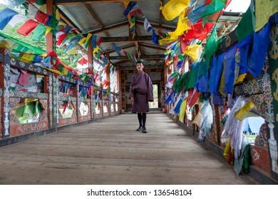 THIMPHU,BHUTAN - SEPTEMBER 22:Bhutanese man in traditional dress surrounded by prayer flags poses on bridge over Wang Cchu river on September 22,2012 in Thimphu,Bhutan.