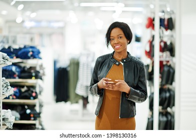Thin african american woman in brown tunic dress and black leather jacket posed at clothes store with phone in hands. It's time for shopping.