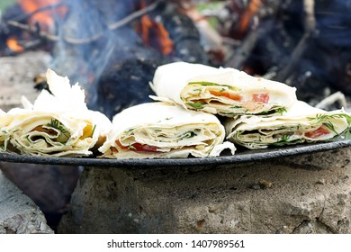 Thin Armenian lavash with tender Suluguni cheese, tomatoes, chicken and salad, grilled. Traditional Middle Eastern snack. Picnic snack.
