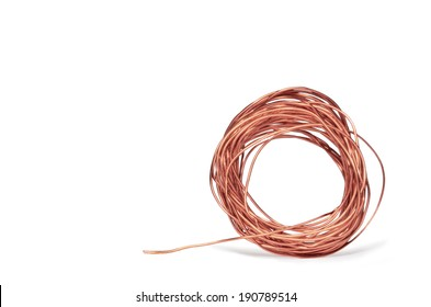 Thin bright copper electrical wire isolated on a white background. Wound in a circle shape with strand extending outward. Drop shadow. Room for text, copy space.