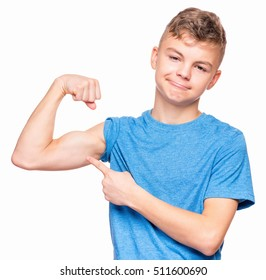 Thin caucasian teen boy wearing blue t-shirt showing off his biceps. Sad teenager showing his hand biceps muscles strength, isolated on white background. Sports theme and childhood concept - child in