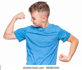 Thin caucasian teen boy wearing blue t-shirt showing off his biceps. Happy teenager showing his hand biceps muscles strength, isolated on white background. Sports theme and childhood concept - child
