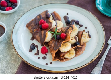 Thin chocolate pancakes stuffed with bananas, raspberries and blueberries, poured with chocolate sauce, on a gray ceramic plate on a light concrete background. Pancake recipes. Pancake day