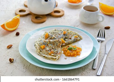 Thin crepe pancakes with poppy seeds, orange jam and chopped hazelnuts on a white plate on a light concrete background. French cuisine. Pancake day concept. Pancake Recipes. Selective focus