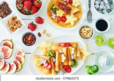 Thin crepes with carambola, pitaya, strawberry, kiwi, banana, figs, lime and honey over white table. Top view of healthy breakfast over white background.