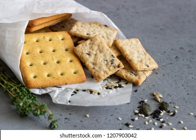 Thin crispy salted crackers with seeds and herbs on grey concrete background.