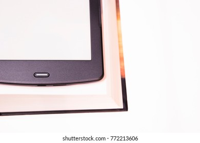 Thin e-book is over a rough paper book. New paper technologies. Replacing paper books. Convenience and comfort of reading. White background. Isolated.