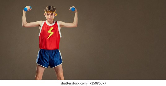 A thin funny guy in sports clothes with small dumbbells