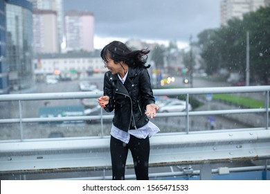 A thin girl in black dodges the gusts of wind and rain. She laughs. Summer rain caught her in the middle of the city.