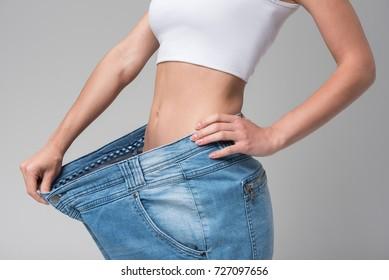 Thin girl keeping large pants