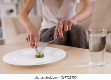 Thin girl is sitting on the sofa with an empty plate which is closeup on the photo. Malnutrition harms health