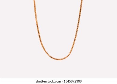 Thin gold chain for women. Snake style necklace isolated on a white background.