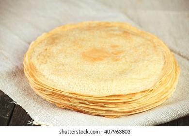 Thin golden crepes pancakes on linen towel. Tasty breakfast.