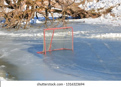 Thin ice and the dangers of playing outside during the winter months is illustrated by a hockey net on a pond while the ice is melting.