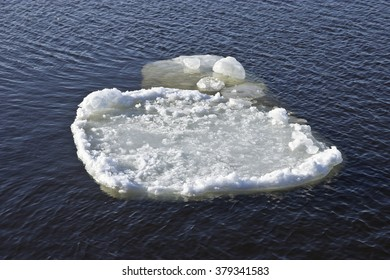 Thin ice floe drifts downstream in springtime