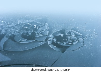 Thin ice on lake, with holes making interesting pattern