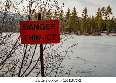 Thin ice sign indicating danger/hazard on frozen over mountain lake (Manzanita Lake in Lassen Volcanic National Park).
