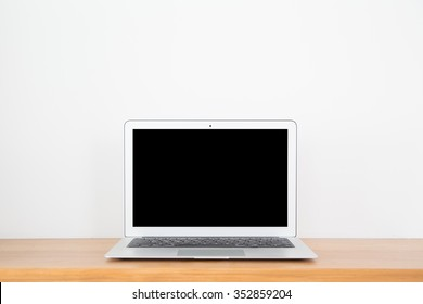 Thin laptop on wood table and white background.