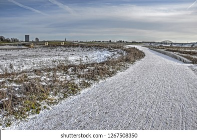 A thin layer of snow covering the floodplain near the city of Nijmegen, The Netherlands, where a path leads along stepping stones and across an elegant concrete bridge