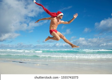 Thin man with extra long Santa hat jumping in red swimming briefs on the shore of a beach in a tropical Christmas celebration
