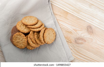 Thin oatmeal cookies or healthy cereal oat crackers with chocolate. Crispy anzac biscuit cookie with oat flakes on rustic table background top view