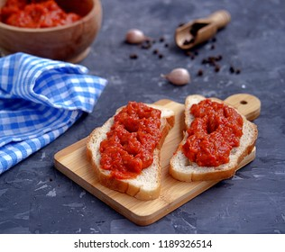 Thin open sandwiches with aivar, snack from baked sweet red pepper and eggplant on white bread. Serbian cuisine.