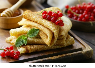 thin pancakes with berries and honey