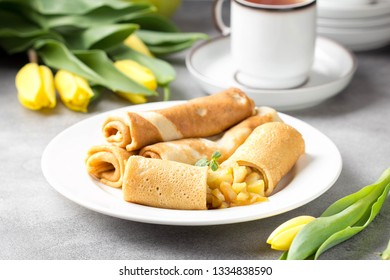 Thin pancakes (crepes) with apple filling, stuffed rolls, Russian traditional food for maslenitsa, French dessert, breakfast with tulips on mother's day