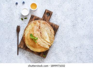 Ccrêpes fines avec crème aigre et miel sur fond bois sur fond béton. Une pile de crêpes. Vue d'en haut.
