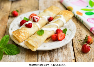 Thin pancakes with strawberries on a wooden background