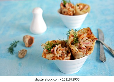 Thin pancakes stuffed with squid, roasted carrots and eggs on a light blue background. Served portions in white bowls, decorated with dill sprigs.