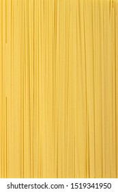 Thin pasta arranged in rows. Yellow italian pasta. Long spaghetti. Raw spaghetti wallpaper. Food background concept.