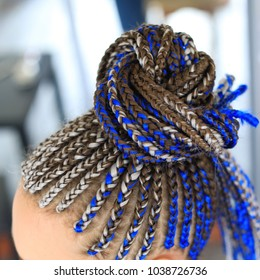 thin pigtails collected in the tail, blue hair, African style close-up, ethnic hairstyle background, youth hairstyle