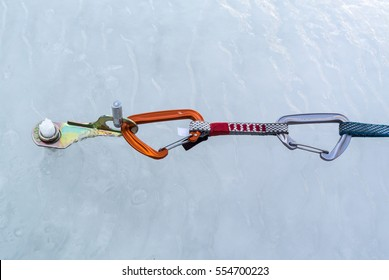 The thin quickdraw with an orange climbing carabiner hooked the ring ice screws screwed into the ice of a frozen waterfall