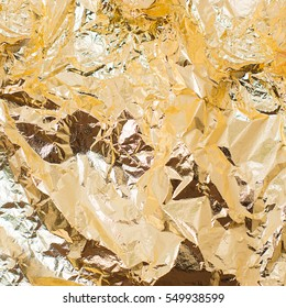 Thin sheet of golden leaf background with shiny uneven surface