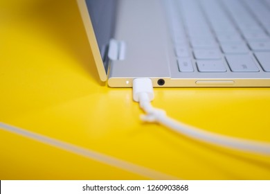 Thin silver laptop closed up on a usb-c charging cable on a yellow desk