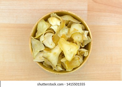 Thin slice dried Brown Lily Bulb, also called Bai He used in traditional Chinese medicine in wooden bowl, top view on wooden background