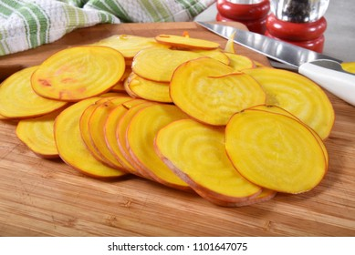 Thin sliced golden beets on a cutting board