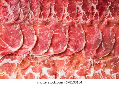 thin sliced pork and beef on wooden plate