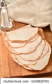 Thin sliced turkey breast meat on a cutting board, high angle view