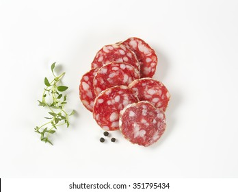 thin slices of french dry salami, thyme and peppercorns on white background