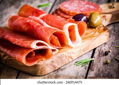 thin slices of prosciutto with olives and salami on wooden cutting board
